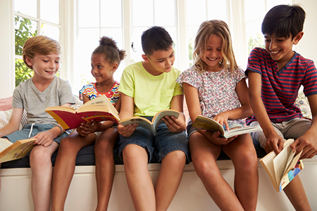 Group Of Multi-Cultural Children Reading On Window Seat